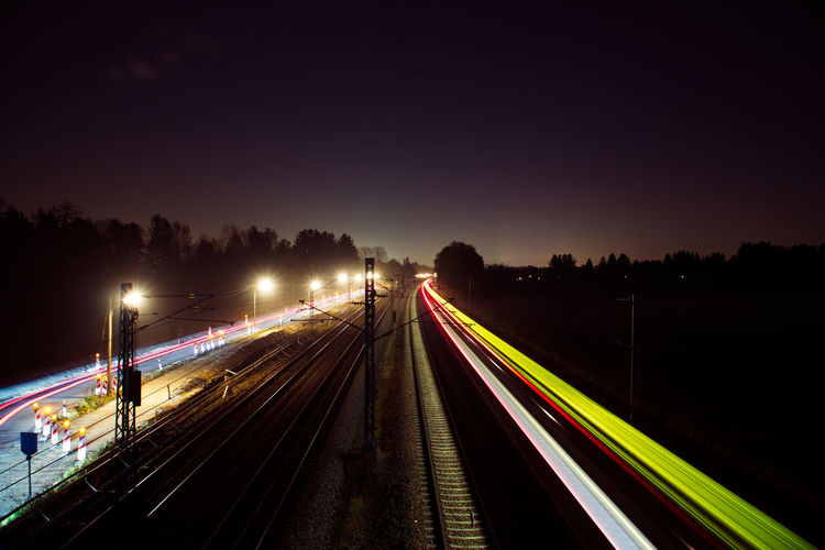 Light trails on railroad tracks against sky at night