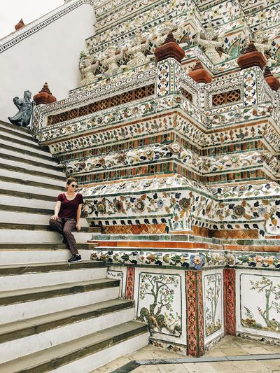 Young woman sitting on staircase outside temple