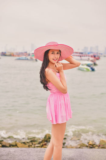 Beach Beautiful Woman Clothing Day Fashion Focus On Foreground Hairstyle Innocence Land Leisure Activity Lifestyles Looking At Camera One Person Outdoors Pink Color Portrait Real People Sea Smiling Standing Three Quarter Length Water Women