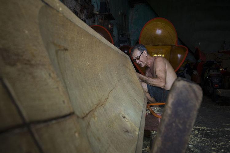 Side view of shirtless senior carpenter working in workshop