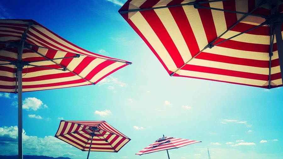 Low angle view of red and white striped parasols at beach against sky