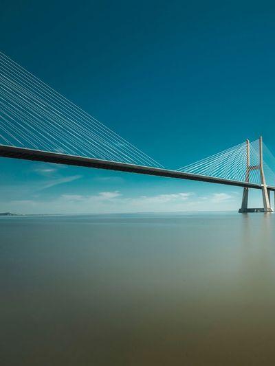 Suspension bridge over sea against blue sky