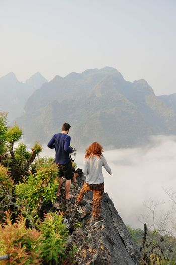Rear view of couple standing on mountain against clear sky