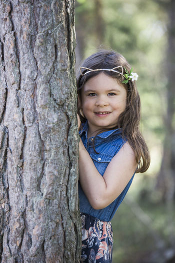 Portrait of a smiling girl against tree trunk