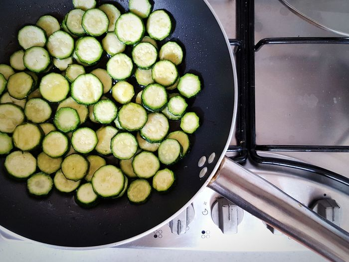 High angle view of zucchini slices cooked on frying pan in kitchen