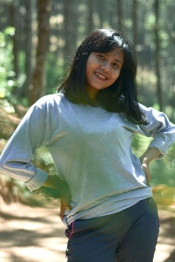 Portrait of a smiling young woman in forest