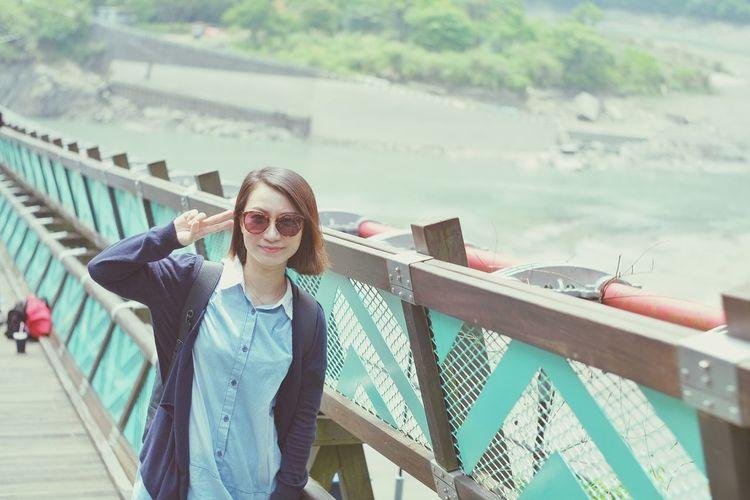 Portrait of mature woman gesturing on footbridge