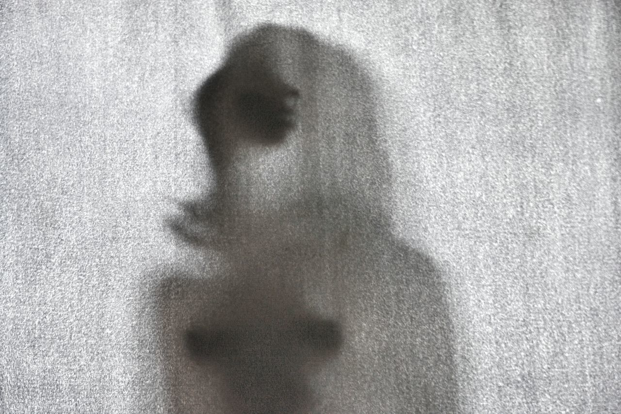 Shadow of woman on curtain at home