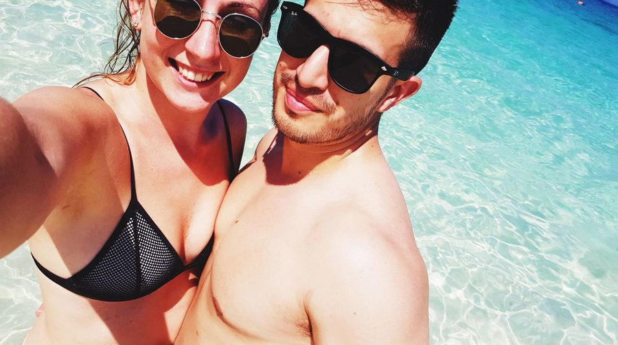 Portrait of couple wearing sunglasses in sea