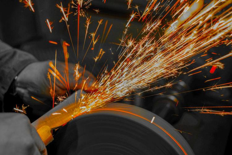 Cropped image of man using circular saw in workshop