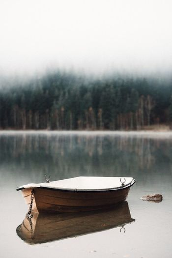Boat moored on lake against trees during foggy weather