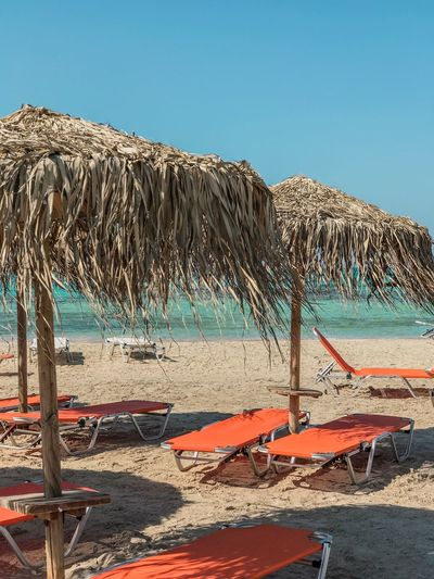 Lifestyles Vacations Relaxing Clear Water Turquoise Water Orange Sunbed Orange Color Straw Straw Umbrella Beach Umbrella Medeteranian Sea Island Crete Sunbed Sky Water Beach Land Nature Sunlight Day Sea Clear Sky Sand No People Beauty In Nature Outdoors Tranquility Tranquil Scene Scenics - Nature