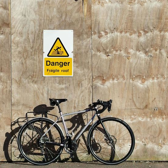 Bike leaning against wall with warning sign