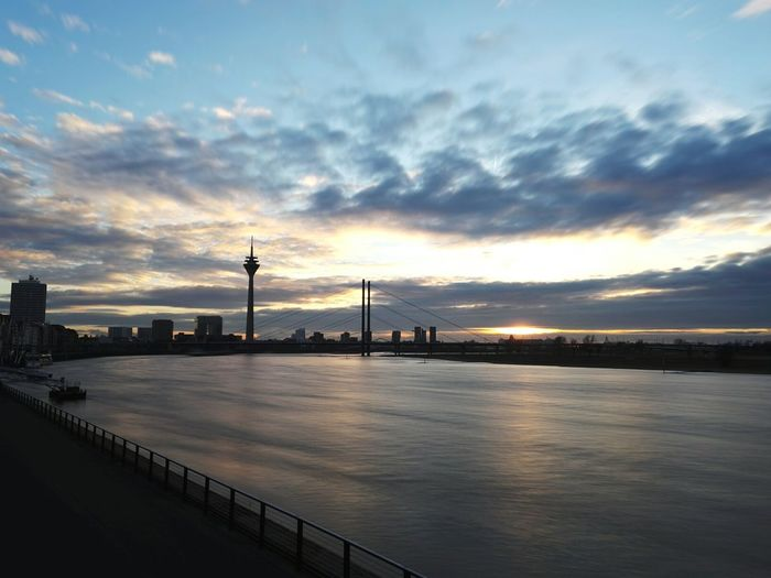 Rheinturm tower and theodor heuss bridge over rhine river during sunset