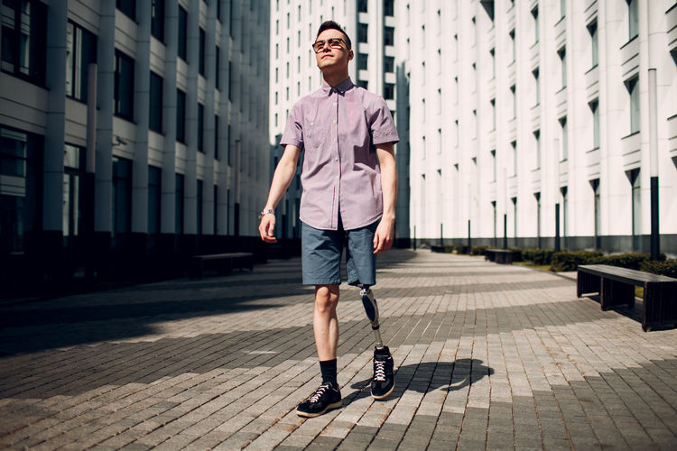Full length man with amputated leg standing in city