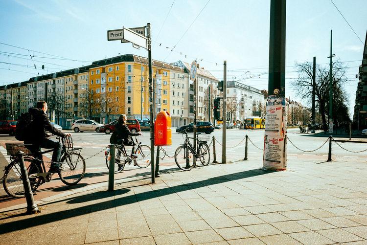 Bicycles on sidewalk by buildings in city against sky