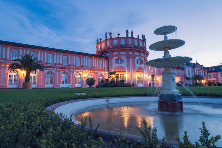 Biebrich castle in the german city of wiesbaden with water fountain at sunset against clear blue sky