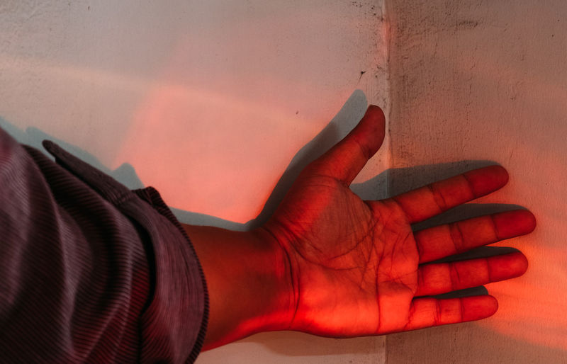 Close-up of hand against red wall