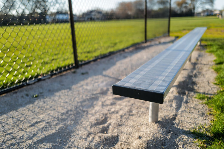 Close-up of empty players bench on baseball field