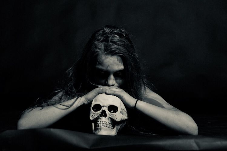 Woman leaning on human skull against black background