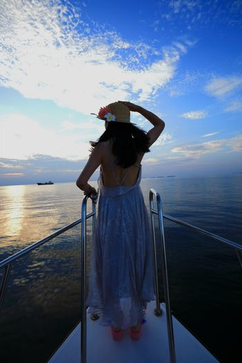 Rear view of woman standing on boat in sea