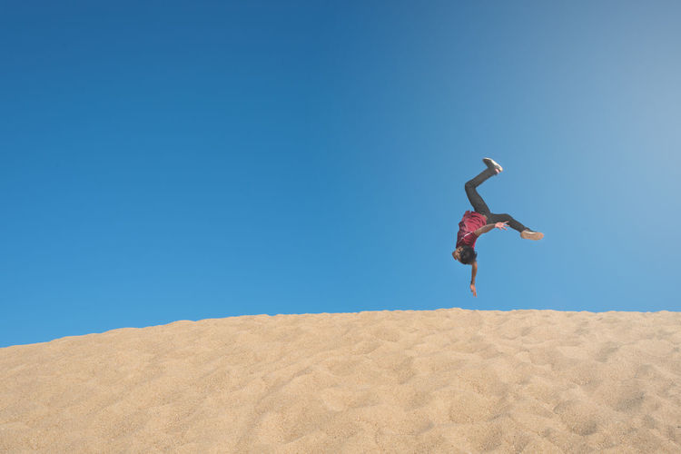 Full length of man jumping upside down on sand against clear blue sky