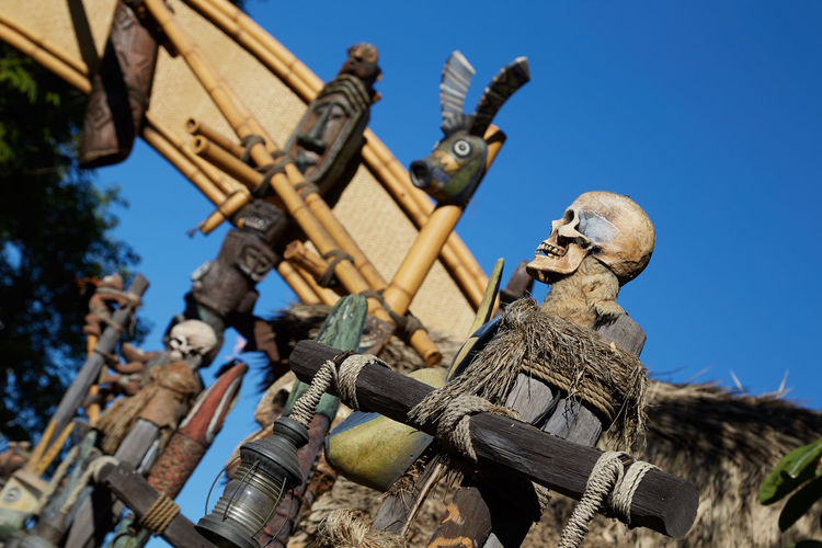 A slanted view. No People Day Low Angle View Sky Wood - Material Outdoors Skull Bamboo Torch Tiki Carving Wood Angle Tilt