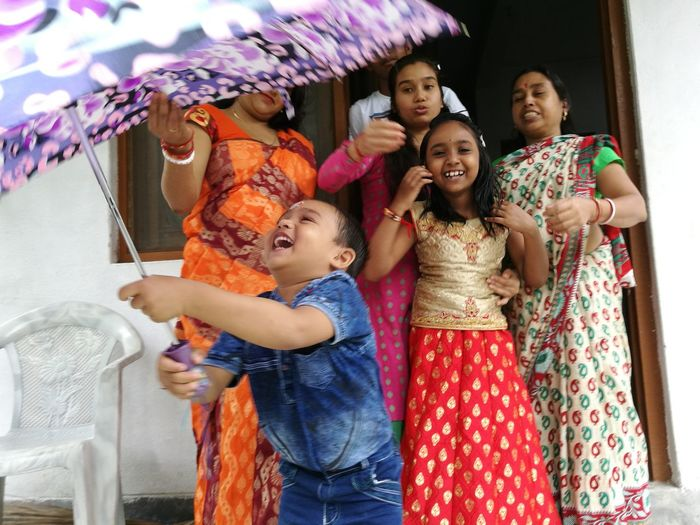Cheerful family with umbrella outside house
