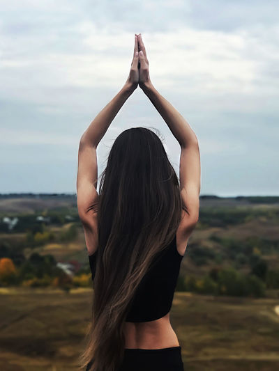 Rear view of woman with arms raised meditating against sky