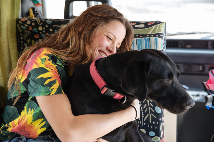Woman Embracing Dog In Camper Van