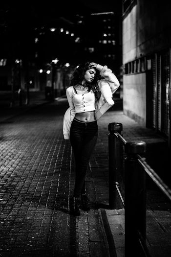 Woman standing on street in city at night