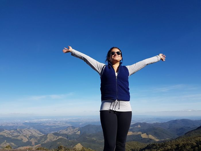 Low Angle View Of Woman With Arms Raised Standing On Mountain Against Blue Sky