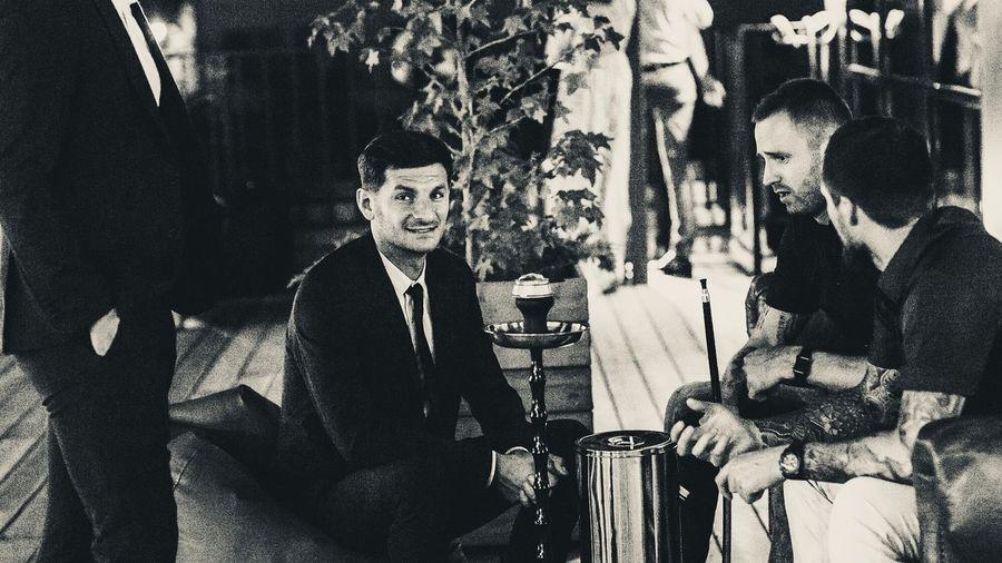 Portrait of man sitting with friends by hookah