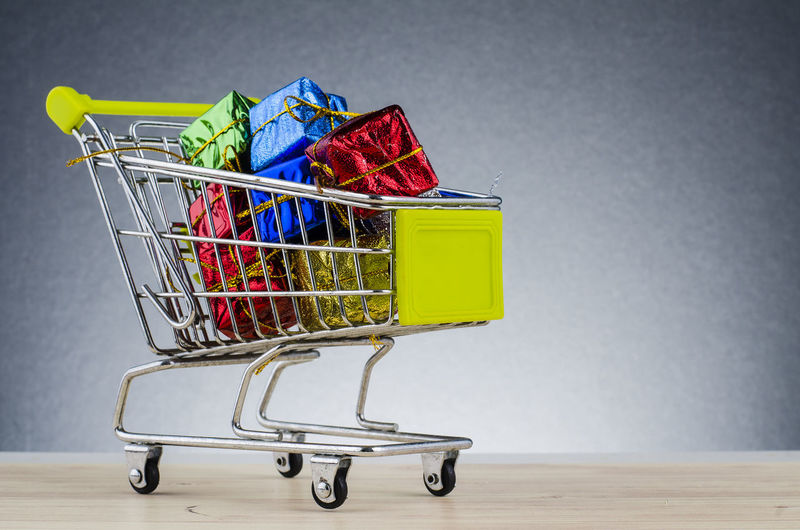 shopping chart on wooden desk over beautiful gradient background with reverberation Shopping Cart Consumerism Shopping Retail  Indoors  No People Still Life Multi Colored Close-up Copy Space Wall - Building Feature Store Container Metal Business Gray Background Bag Variation Group Of Objects Large Group Of Objects Groceries