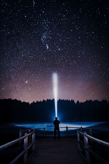 Rear view of man holding illuminated flashlight while standing against sky at night