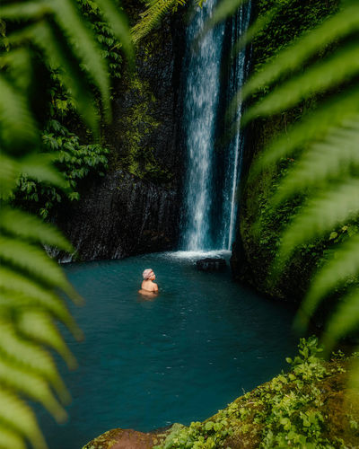 High angle view of woman enjoying waterfall in forest
