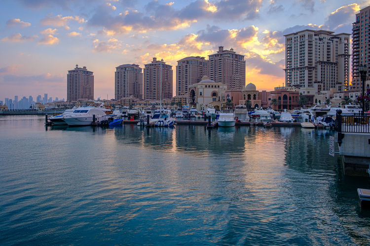 Boats moored in sea against buildings in city during sunset