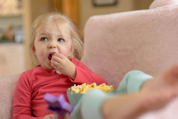 Little blonde girl eating popcorn while watching tv Expression Face Little Girl Relaxing Sofa Couch Home Girl Child Watching A Movie Watching Tv Popcorn Kid