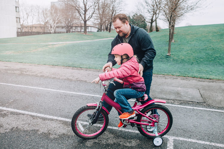 Man assisting daughter in riding bicycle on walkway