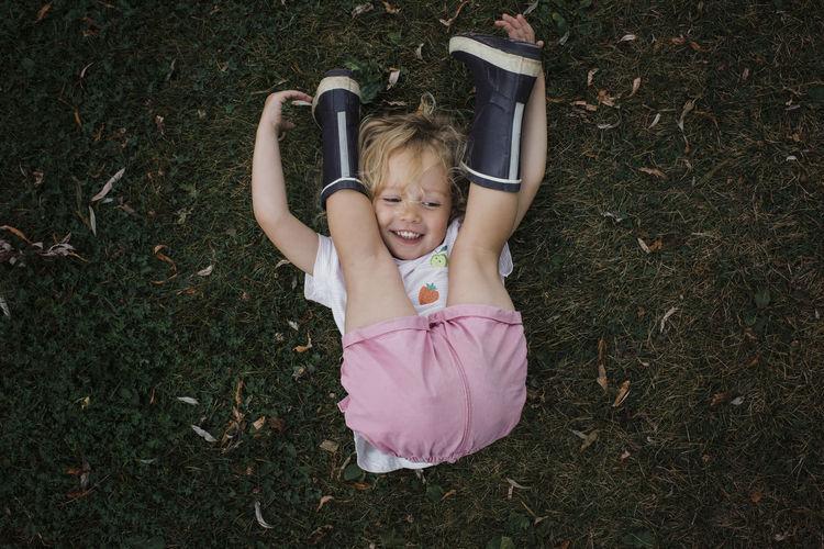 High angle portrait of smiling girl lying down on land