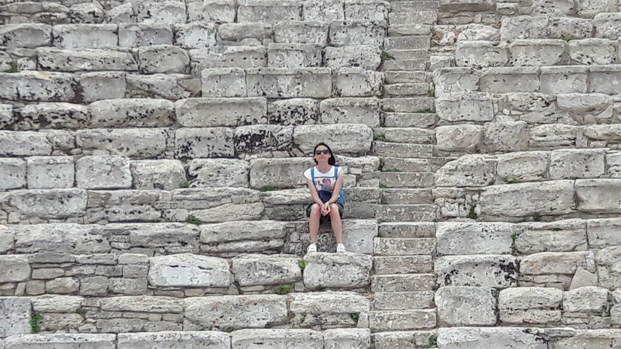 Segesta Young Women Men Standing Leaning Brick Wall Full Length Relaxation Architecture Built Structure Building Exterior Stone Wall Old Ruin Archaeology Archway Amphitheater Ancient Civilization Ancient Stone Material Historic Ruined