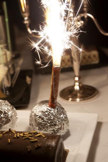 Close-Up Of Lit Sparkler On Dessert
