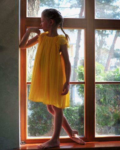 Full length of woman looking through window