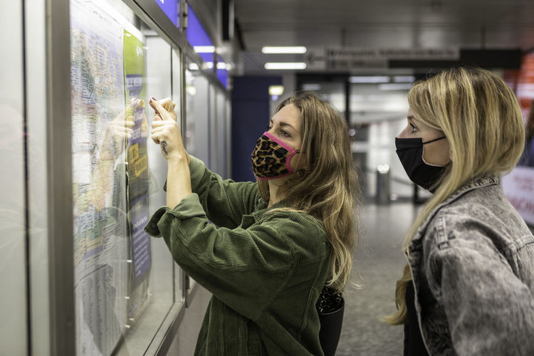 Female friends wearing masks looking map at station