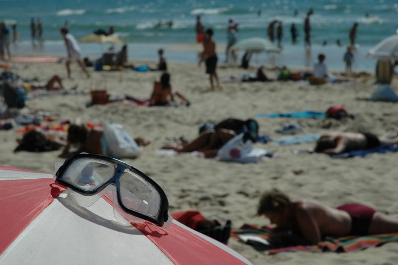 Close-up of swimming goggles on beach