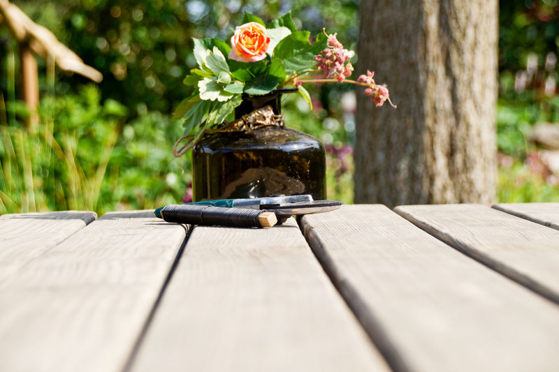 Surface level of flower vase with string and pruning shears on wooden table
