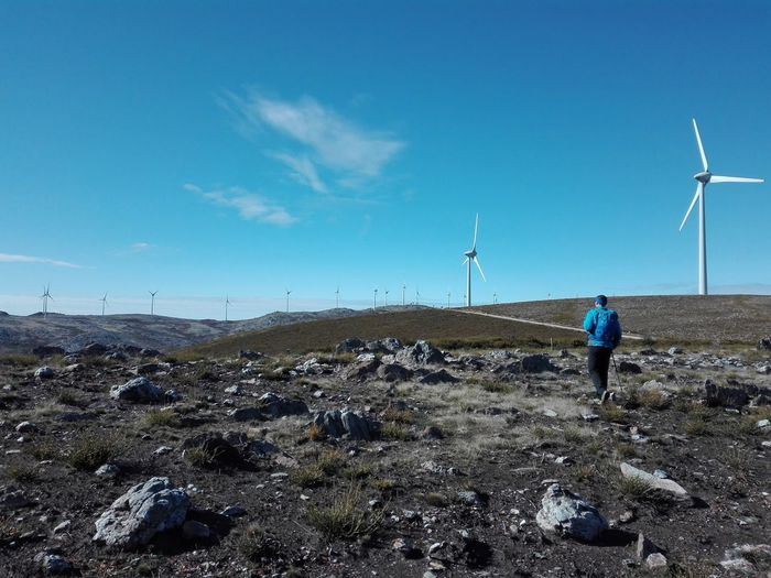 Blue Sky Trekking Walking Sunny Day One Person One Man Only Fuel And Power Generation Wind Turbine Alternative Energy Sky Wind Power Outdoors Day