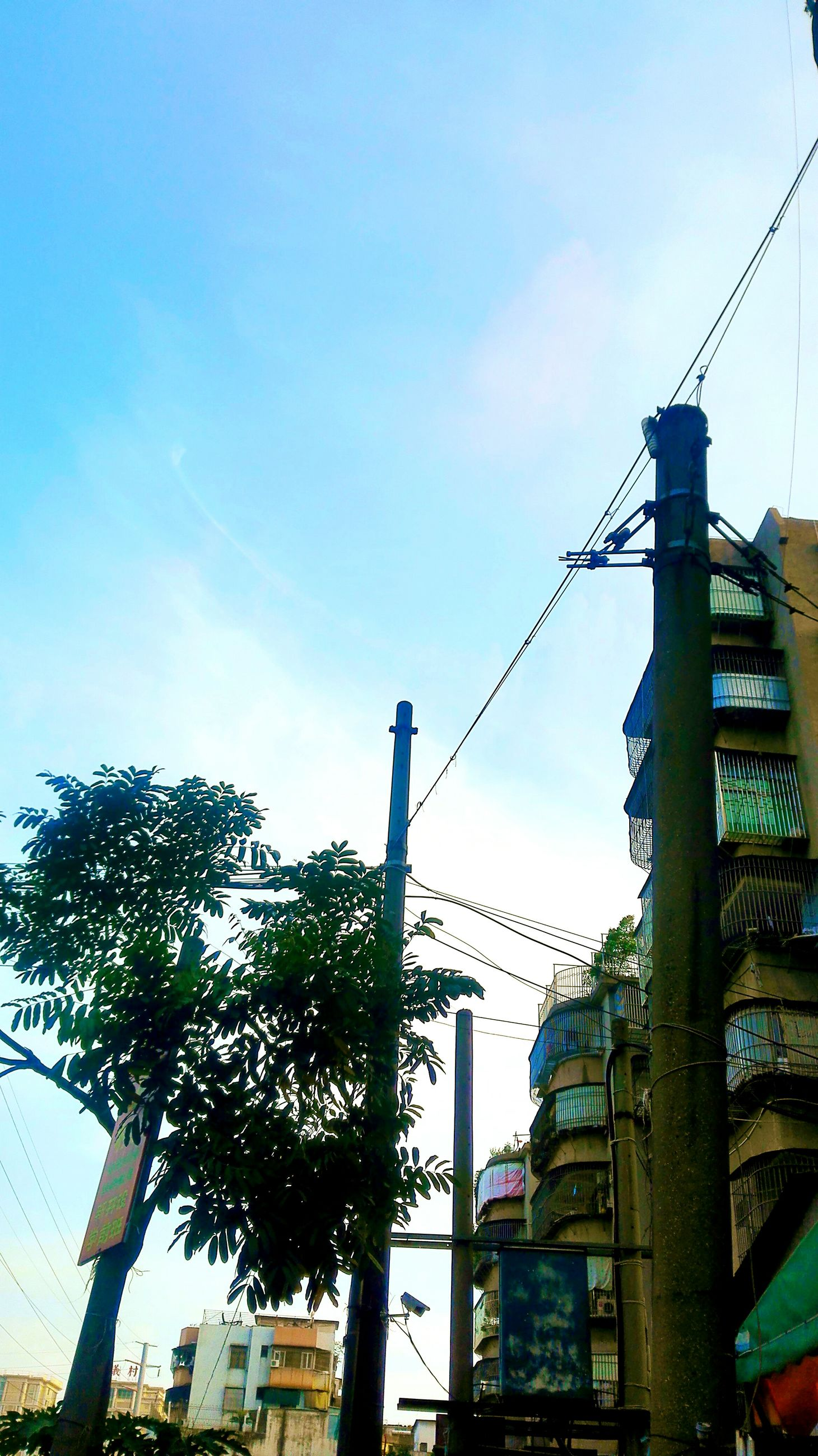 building exterior, architecture, built structure, low angle view, sky, city, street light, building, clear sky, construction site, tall - high, outdoors, sunlight, development, blue, industry, residential building, day, power line, crane - construction machinery