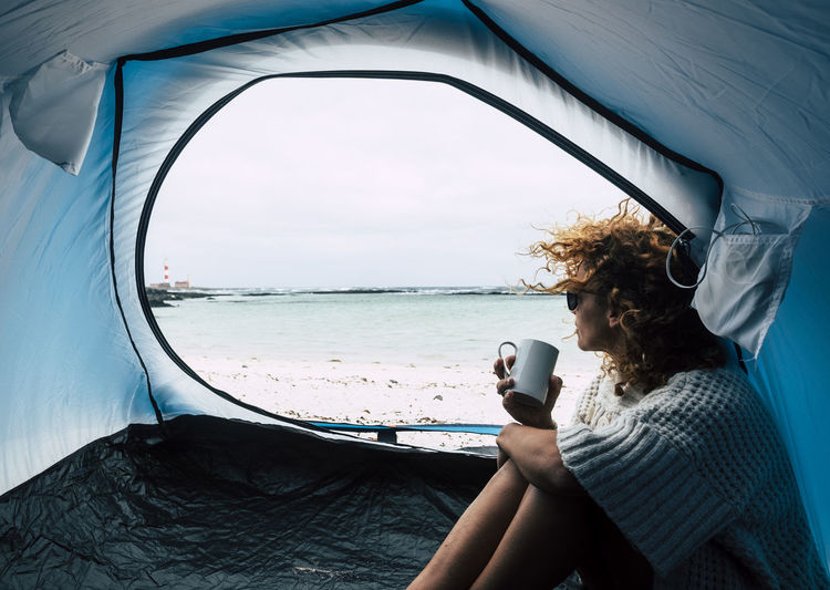 Woman looking at sea while sitting in tent