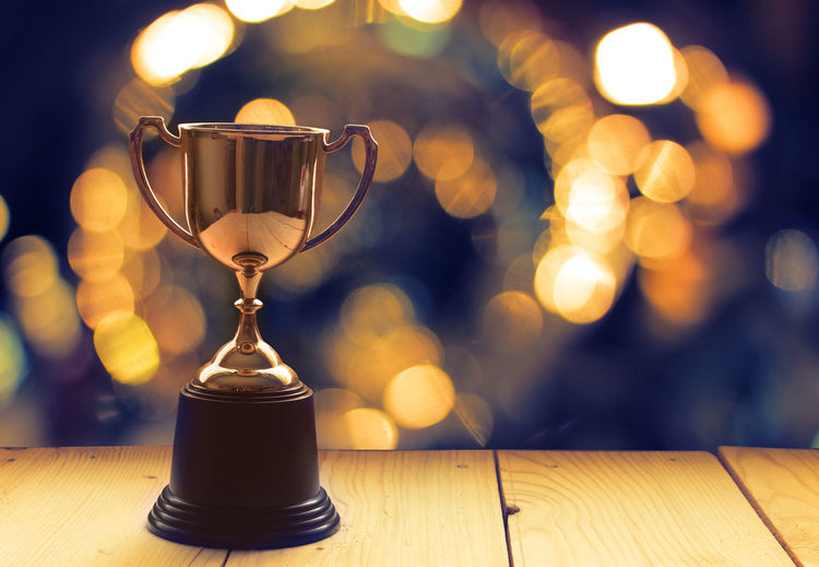 Close-up of golden trophy on wooden table against defocused background
